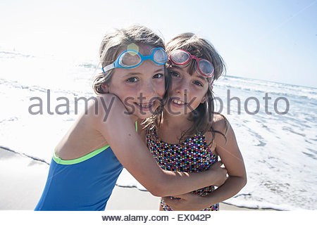 Portrait of twin sisters hugging on beach, Del Mar, California, USA - Stock Photo