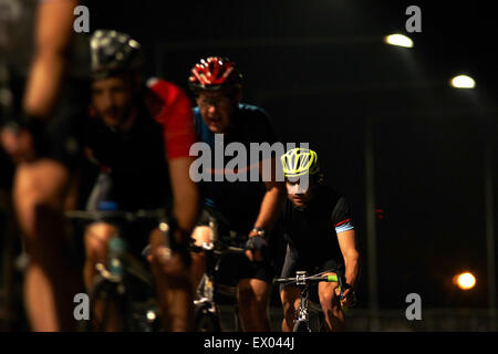 Cyclists cycling on track at velodrome, outdoors - Stock Photo