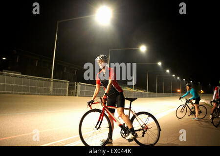 Cyclists on track at velodrome, outdoors - Stock Photo