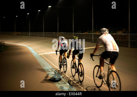 Cyclists cycling on track at velodrome, rear view - Stock Photo
