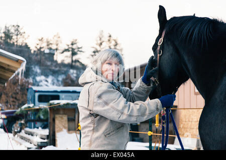 Senior adult woman standing with horse in snowy landscape - Stock Photo