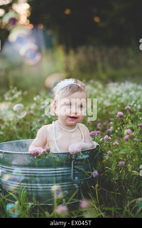 Portrait of baby girl bathing in a tin bathtub in a wild flower meadow - Stock Photo