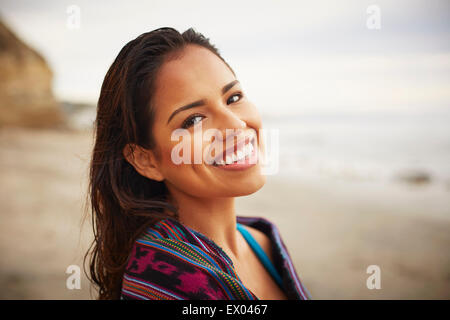 Portrait of smiling young woman wrapped in towel on beach, San Diego, California, USA - Stock Photo