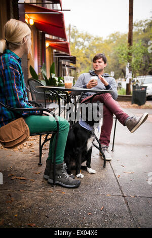 Couple with dog having coffee at sidewalk cafe, Savannah, Georgia, USA - Stock Photo