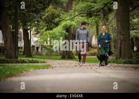 Couple walking dog in park, Savannah, Georgia, USA - Stock Photo