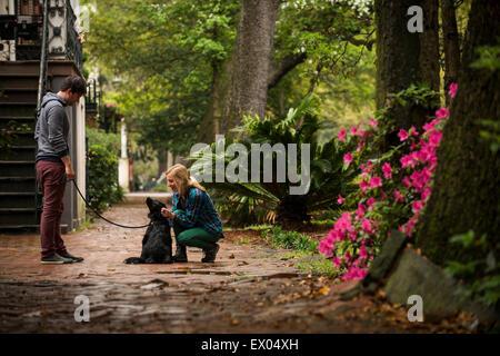 Couple with dog behind house, Savannah, Georgia, USA - Stock Photo