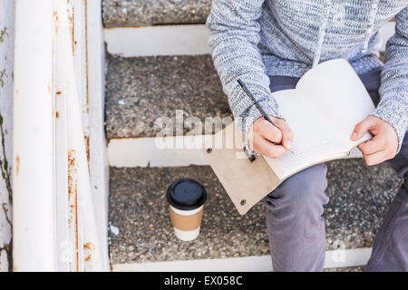 Man sitting on steps writing in notebook - Stock Photo