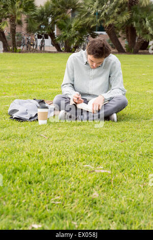 Businessman sitting in park, writing - Stock Photo
