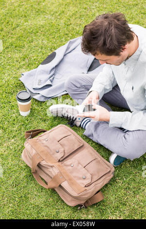 Businessman using cell phone in park, high angle - Stock Photo