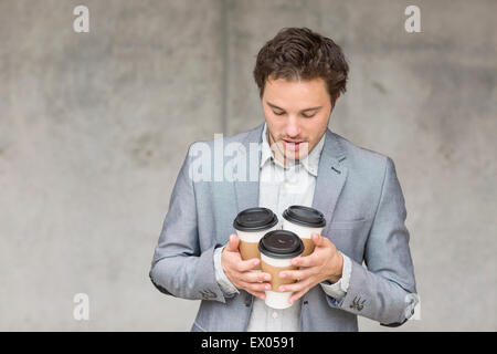 Businessman holding disposable coffee cups - Stock Photo