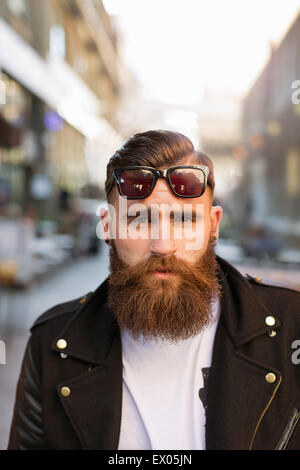 Portrait of bearded young man with sunglasses - Stock Photo