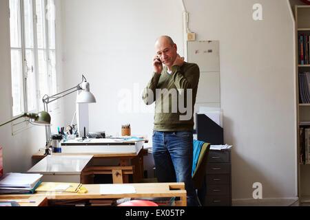 Mature man on the phone in creative studio - Stock Photo