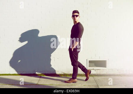 Young man walking past white wall - Stock Photo