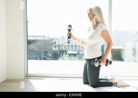 Senior woman exercising with dumbbells - Stock Photo