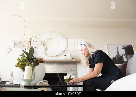 Senior female businesswoman using laptop in living room - Stock Photo