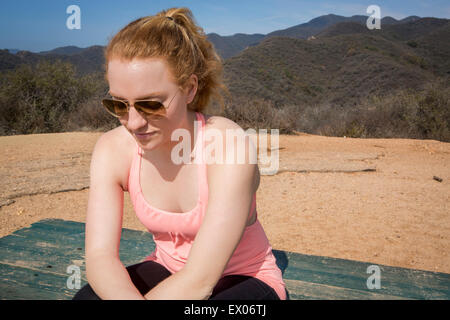 Young female runner sitting on bench taking a break - Stock Photo