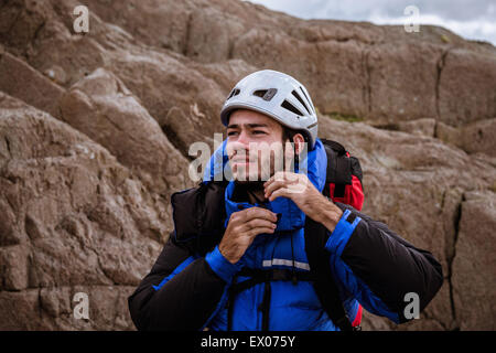 Young male climber on rock fastening helmet, The Lake District, Cumbria, UK - Stock Photo