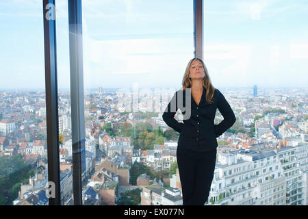 Tired businesswoman in front of office window with Brussels cityscape, Belgium - Stock Photo