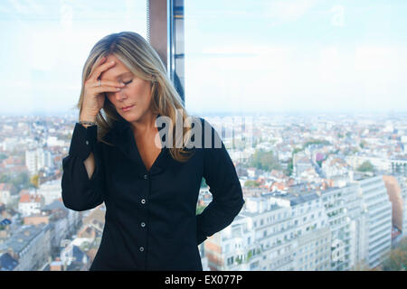 Stressed businesswoman in front of office window with Brussels cityscape, Belgium - Stock Photo