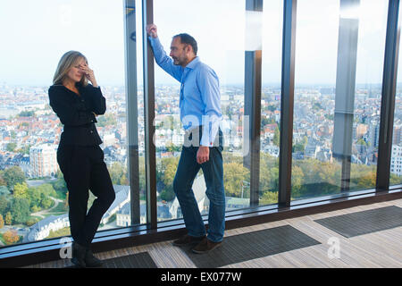 Stressed businesswoman and man in skyscraper office, Brussels, Belgium - Stock Photo