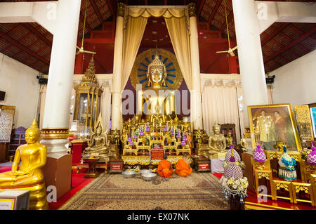 Young monks at prayer in front of the main altar of the Wiharn Luang at Wat Phra Singh, Chiang Mai - Stock Photo