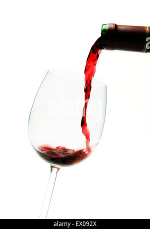 Red wine being poured from a bottle into a glass. - Stock Photo