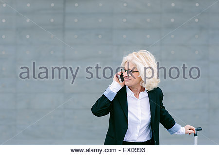 Mature businesswoman with suitcase, using mobile phone - Stock Photo