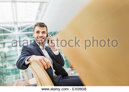 Young businessman in airport departure lounge chatting on smartphone - Stock Photo
