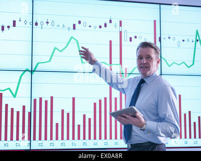 Businessman making presentation in front of graphs on screen, portrait - Stock Photo