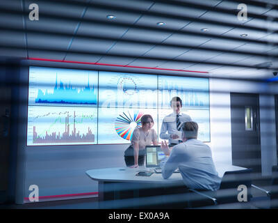 Business colleagues discussing graphs on screen in meeting room - Stock Photo