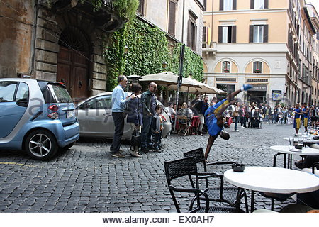 Street performer doing a handstand on a cobbled street in Rome Italy - Stock Photo