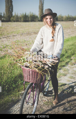 Young woman carrying bunch of sticks on bicycle - Stock Photo