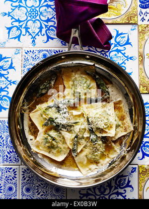 Still life with pan of Italian stinging nettle tortellini and parmesan - Stock Photo