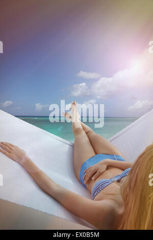 Over the shoulder view of young woman reclining on hammock on Miami Beach, Florida, USA - Stock Photo
