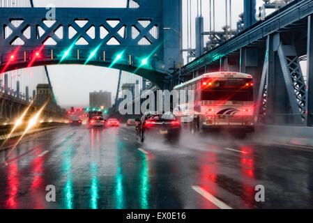 Hazardous driving conditions on a busy bridge during a heavy rain storm. - Stock Photo