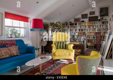 Yellow winged back armchair, Julep chair and bold blue sofa in living room with uzbek kilim, aboriginal art and - Stock Photo