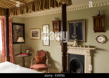 Georgian four poster bed in bedroom with Louis XV armchair and fireplace - Stock Photo