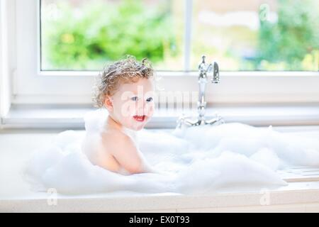 Happy laughing baby girl having fun playing with water and foam in a kitchen sink next to a window - Stock Photo