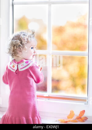 Beautiful toddler girl standing next to a window into the garden with yellow autumn trees - Stock Photo