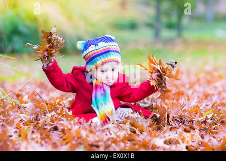 Adorable toddler girl with a colorful scarf and hat playing with red leaves in an autumn park - Stock Photo