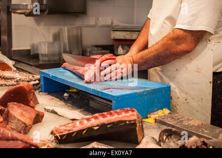 a fishmonger preparing and cutting fresh fish on market - Stock Photo
