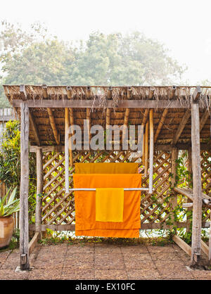 Monk robes hang in the private garden of Room #506, La Residence Phou Vao. Luang Prabang, Laos. - Stock Photo