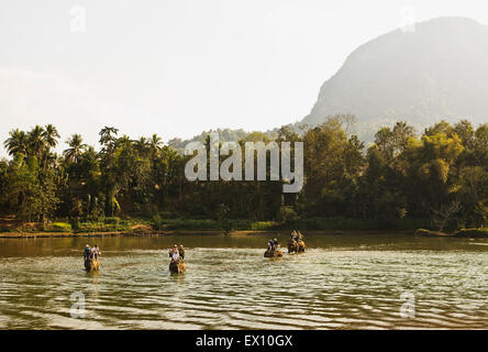 Tourists ride elephants on the Khan River. Luang Prabang, Laos. - Stock Photo