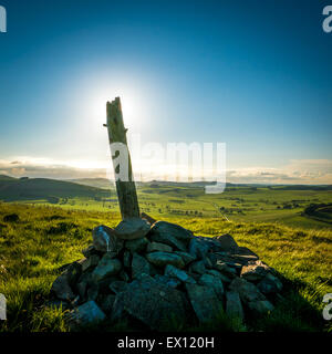 Stones And A Wooden Post At The Summit Of A Hill In Rural Scotland At Sunset - Stock Photo