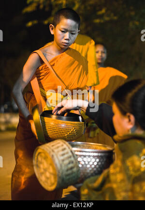 Monk processing for alms in the early morning, a 1,000-year old tradition in Luang Prabang, Laos. - Stock Photo