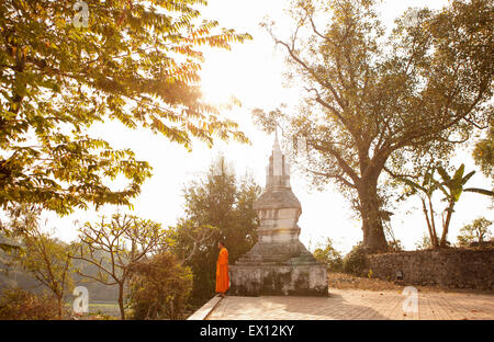 A young monk by Wat Siphoutthabat Thipphuramm at dawn. Luang Prabang , Laos. - Stock Photo