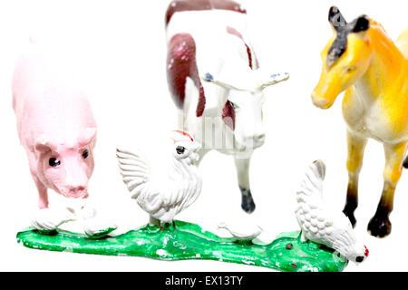 Plastic toy farm animals isolated on white depicting farm life - Stock Photo