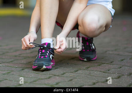 Young woman is tying the laces before running. Close-up, running, healthy lifestyle. - Stock Photo