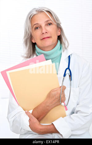 MODEL RELEASED. Mature female doctor holding files, portrait. - Stock Photo