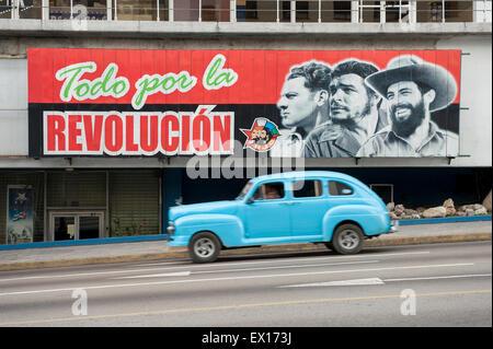 HAVANA, CUBA - JUNE, 2011: Vintage American taxi car passes below billboard promoting Communist propaganda in the - Stock Photo